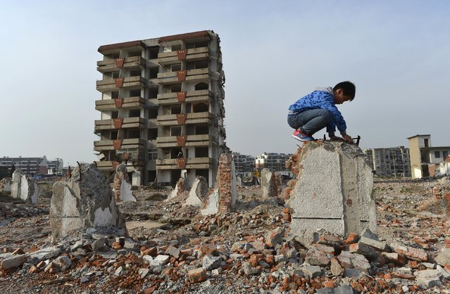 A boy plays on a broken wall next to a partially demolished building at a demolition site making way for a new residential area, in Hefei, Anhui province April 22, 2015. More than a dozen families in the area have been living in these partially demolished buildings, or nail houses, surrounding by ruins for more than two years as they did not reach agreements with developers regarding their compensations, local media reported. (Photo by Reuters/Stringer)