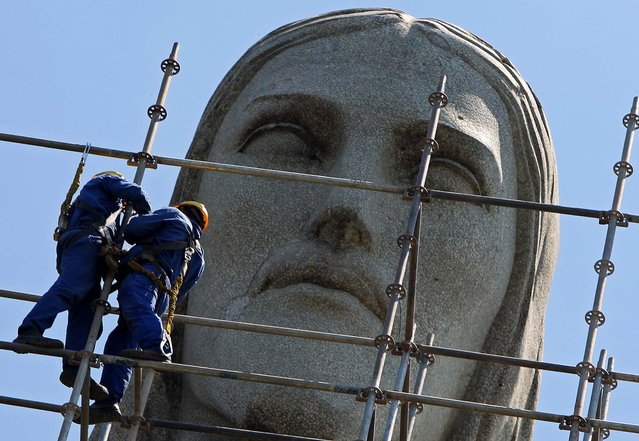 Men work on the scaffoldings surrounding the Christ the Redeemer statue on March 12, 2010.The iconic statue that was inaugurated in 1931got a $4 million renovation. Heavy rains had eroded portions of its face and hands and it had also been damaged by lightning strikes over the years. (Photo by Felipe Dana/Associated Press)