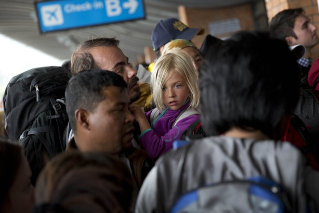 A German national girl and a man wait in a queue to go inside the Kathmandu international airport, in Kathmandu, Nepal, Sunday, April 26, 2015. (Photo by Bernat Armangue/AP Photo)