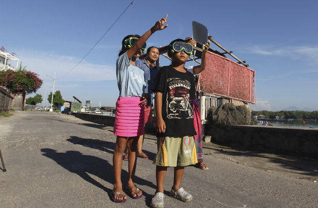 """Children wear goggles to watch a solar eclipse in the sky during Nyepi, the annual """"Day of Silence"""" during which Balinese Hindus welcome the New Year in Bali, Indonesia, Wednesday, March 9, 2016. People gazed at the sky in wonder and cheered while others knelt in prayer as a total eclipse of the sun unfolded over Indonesia on Wednesday. (Photo by Firdia Lisnwati/AP Photo)"""