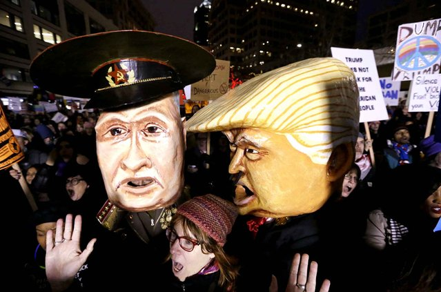 A woman shouts out as she stands in front of giant puppet heads portraying Vladimir Putin and Donald Trump at rally to oppose Trump's executive order barring people from certain Muslim nations from entering the United States, Sunday, January 29, 2017, in downtown Seattle. (Photo by Elaine Thompson/AP Photo)