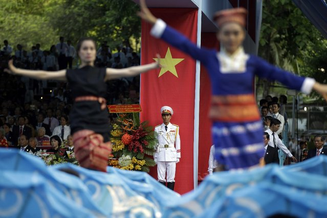 """An honor guard stands in attention as dancers perform during parade celebrating the 40th anniversary of the end of the Vietnam War which is also remembered as the """"Fall of Saigon"""", in Ho Chi Minh City, Vietnam, Thursday, April 30, 2015. (Photo by Dita Alangkara/AP Photo)"""
