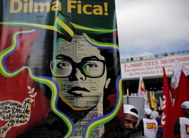 A man holds a banner with an image depicting Brazil's President Dilma Rousseff during a rally to commemorate International Workers' Day, in Sao Paulo May 1, 2015. (Photo by Nacho Doce/Reuters)