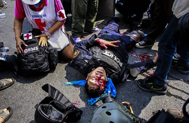 A riot police officer lies motionless after a massive head injury during a clash with protesters in Bangkok, Thailand, on February 18, 2014. Hundreds of riot police attempted to clear out anti-government protest sites around Thailand's capital on Tuesday, triggering clashes that left three people dead and 57 others injured. (Photo by Wally Santana/Associated Press)