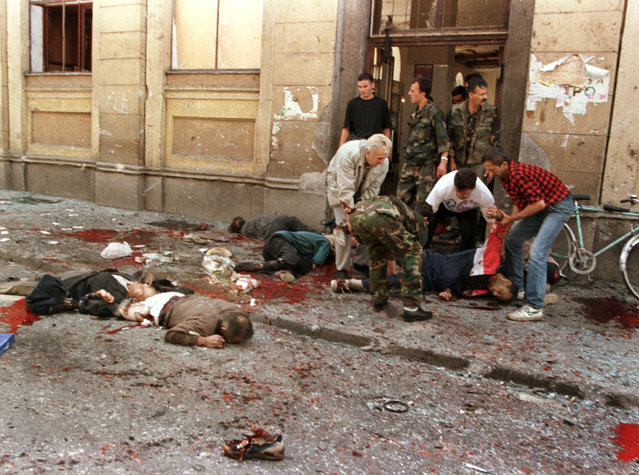 People look for wounded outside of the indoor market at the site of a mortar blast in the center of Sarajevo that killed some 40 people, August 28, 1995. (Photo by Peter Andrews/Reuters)
