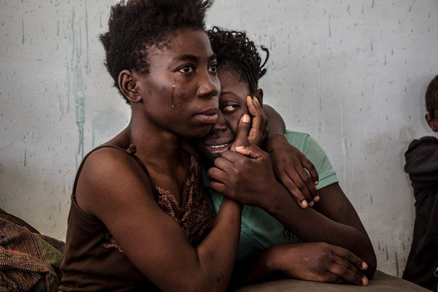 Two Nigerian refugees cry and embrace in a detention center for refugees in Surman, Libya 17 August 2016. The detention center houses hundreds of women escaping precarious conditions. Many claim they are regularly beaten or sexually assaulted, and receive insufficient amounts of food and water at the center. Most of these women were attempting to reach Europe by being smuggled across the Mediterranean in boats setting sail from neighboring Sabratah. (Photo by Daniel Etter/Reuters/Courtesy of World Press Photo Foundation)