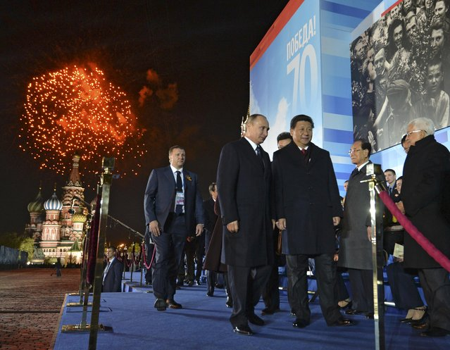 Russia's President Vladimir Putin (2nd L) and China's President Xi Jinping (C) leave a festive concert marking the 70th anniversary of the end of World War Two in Europe, as fireworks explode over Red Square in Moscow, Russia, May 9, 2015. (Photo by Alexei Druzhinin/Reuters/RIA Novosti/Kremlin)