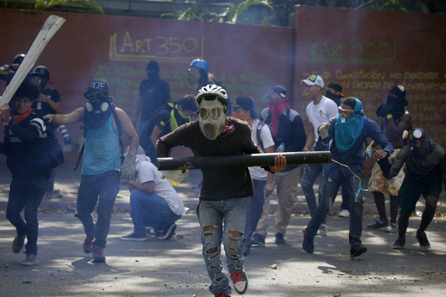 Anti-government protesters, one carrying a homemade mortar, take cover as security forces fire tear gas to disperse demonstrators in Caracas, Venezuela, Wednesday, May 1, 2019. (Photo by Fernando Llano/AP Photo)