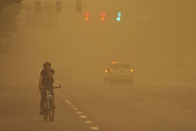 A man covers his face as he rides a bicycle along a street during a sandstorm, in Wujiaqu, Xinjiang Uighur Autonomous Region April 27, 2015. Affected by the cold air, large areas of Xinjiang saw dusty weather from Monday, and the temperature will fall by eight degree centigrade, according to local meteorological authorities, state television reported. (Photo by Reuters/Stringer)