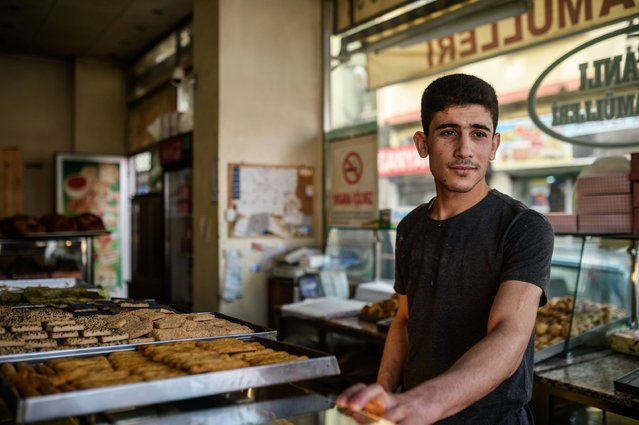 Baker Assad, 22, poses as he dreams about crossing to Europe on March 13, 2016 in Gaziantep, Turkey. He said that after five years of scraping a living selling bread on the streets, his sights are set on making the journey with his family. Many Syrians in Gaziantep, unaware of the EU-Turkey deal, are planning to head to Europe. Nearly 150,000 people have made the sea crossing from Turkey to Greece already this year, according to the UN, but the passage is dangerous – hundreds have died in the attempt. (Photo by Ozan Kose/AFP Photo)