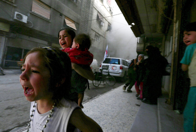 Children react after what activists said was shelling by forces loyal to Syria's President Bashar al-Assad near the Syrian Arab Red Crescent center in the Douma neighborhood of Damascus May 6, 2015. (Photo by Bassam Khabieh/Reuters)