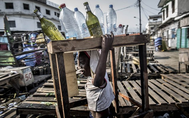 """A boy carries empty bottles as he walks past empty stalls during a """"dead city"""" strike called by five defeated opposition candidates to protest the re-election of President Denis Sassou Nguesso, in Brazzaville on March 29, 2016. (Photo by Marco Longari/AFP Photo)"""