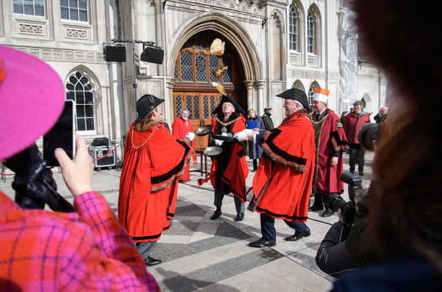 The Lord Mayor of London (C) joins others as they flip pancakes ahead of the annual Inter-Livery Pancake Race at The Guildhall on February 28, 2017 in London, England. The race sees 24 teams from London's traditional companies of craftspeople take part in a pancake-tossing race, while dressed in either their ceremonial robes or novelty costumes. (Photo by Leon Neal/Getty Images)