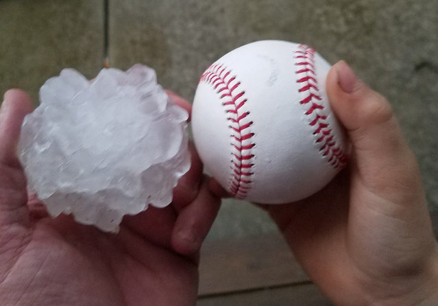This photo provided by Tim Creedon shows his baseball and a hailstone that fell in the backyard of Creedon's home in Ottawa, Ill., Tuesday, February 28, 2017. Illinois Gov. Bruce Rauner has activated the state's emergency operations center as local officials reported damage from tornados spawned by a late-winter storm system. (Photo by Tim Creedon via AP Photo)