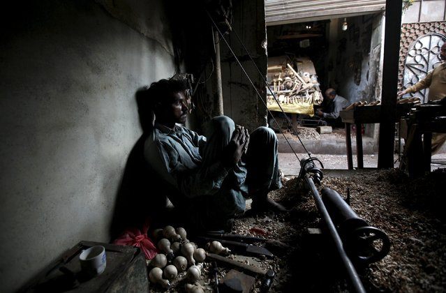 A carpenter at a workshop pauses during a power outage in Karachi April 9, 2015. (Photo by Akhtar Soomro/Reuters)
