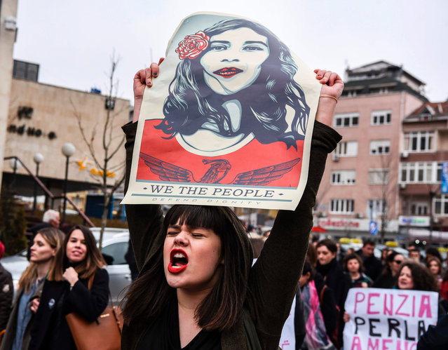 "A woman holds a poster by US artist Shepard Ferey and reading ""We the people, defend dignity"" as Kosovo feminist supporters take part in a rally for gender equality and against violence towards women to mark the International Women's Day in Pristina on March 8, 2017. (Photo by Armend Nimani/AFP Photo)"