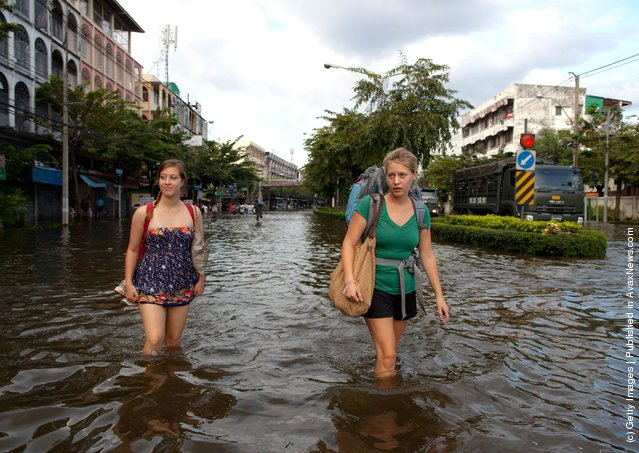 American students from the Thammasat University walk down newly flooded streets near the Chao Phraya river