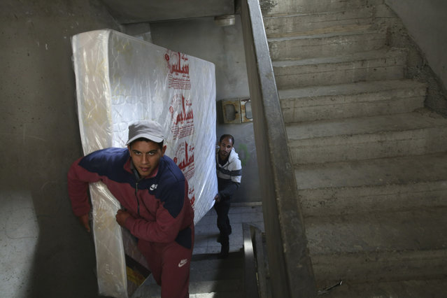 In this April 21, 2019 photo, Palestinian groom Yehiya Taleb, center, move a mattress, part of his wedding furniture, to his apartment in Shati refugee camp, Gaza City. Hundreds of young men in the Gaza Strip have turned to a small industry of lenders to help them pay for their weddings. Taleb got a job working as a waiter at a cafe earning about $180 a month, but that amount was not enough to cover wedding expenses so he took out a $2,000 package through the Farha Project, one of the wedding financing companies. (Photo by Adel Hana/AP Photo)