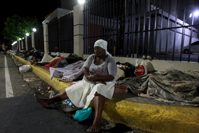 "A Haitian woman sits on a sidewalk outside the Ministry of Interior and Police while waiting along with others to register in Santo Domingo June 17, 2015. A deadline for enforcement of a new immigration law on Wednesday night is raising fears in the Dominican Republic of mass deportations of thousands of Haitian migrants as well as stateless Dominicans of Haitian descent. Dominican officials say anyone lacking proper identity documents or who has not registered for a so-called ""regularization"" program before the deadline could face deportation.  REUTERS/Ricardo Rojas"