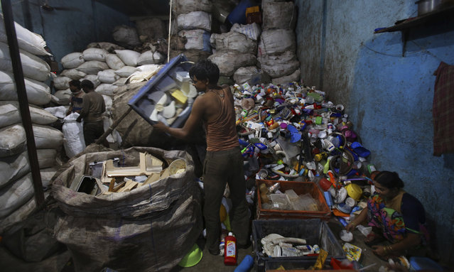 Indian workers sort used plastic at a recycling unit in Mumbai, India, Sunday, July 21, 2019. (Photo by Rafiq Maqbool/AP Photo)
