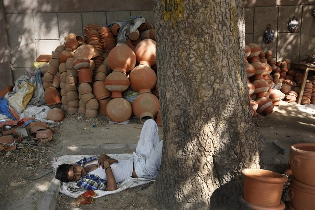 An Indian vendor sleeps near earthen pots on a hot summer day in New Delhi, India, Thursday, May 21, 2015. (Photo by Manish Swarup/AP Photo)