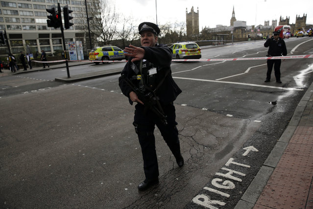"""Police secure the area close to the Houses of Parliament in London, Wednesday, March 22, 2017. The leader of Britain's House of Commons says a man has been shot by police at Parliament. David Liddington also said there were """"reports of further violent incidents in the vicinity"""". London's police said officers had been called to a firearms incident on Westminster Bridge, near the parliament. Britain's MI5 says it is too early to say if the incident is terror-related. (Photo by Matt Dunham/AP Photo)"""