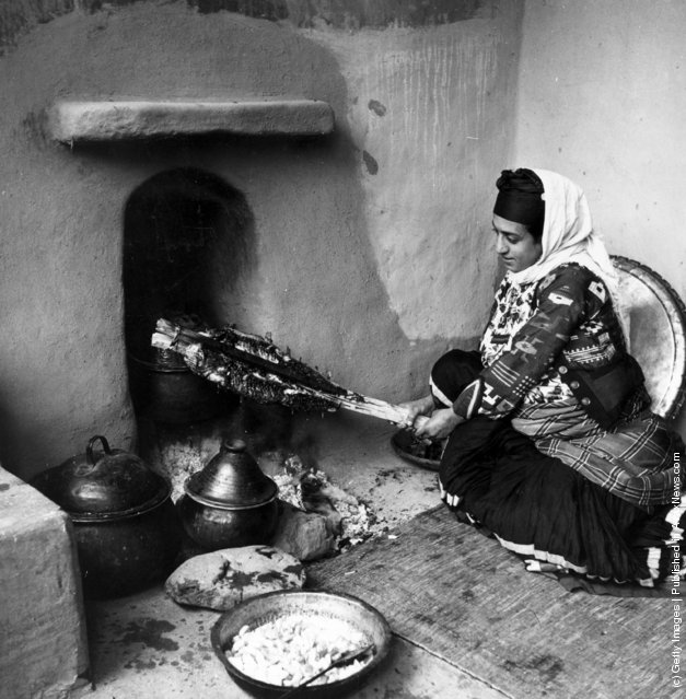 1950:  A peasant woman roasts a joint of meat in the Muslim manner, in the Mazanderan province of northern Iran