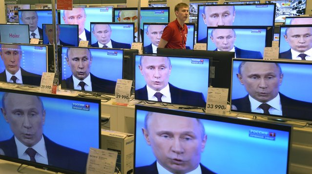An employee walks past TV screens in a shop in Moscow, on April 17, 2014, during the broadcast of President Vladimir Putin's televised question and answer session with the nation. Putin accused today Ukraine's new authorities of driving the country towards the abyss but said that dialogue was the only way out of the intensifying crisis. (Photo by Alexander Nemenov/AFP Photo)