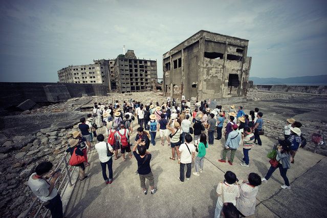 "In this June 29, 2015 photo, tourists visit a part of Hashima Island, commonly known as Gunkanjima, which means ""Battleship Island"", off Nagasaki, Nagasaki Prefecture, southern Japan. (Photo by Eugene Hoshiko/AP Photo)"