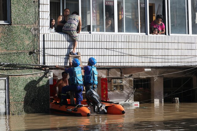 Rescue workers help residents stranded in a building partially submerged by floodwaters after Typhoon Lekima hit the city of Linhai in Taizhou, Zhejiang province, China on August 11, 2019. (Photo by Reuters/China Stringer Network)
