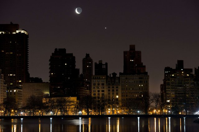 A crescent moon and Venus rise in the pre-dawn hours over the east side of Manhattan March 27, 2014 in this view over the reservoir in New York's Central Park. (Photo by Stan Honda/AFP Photo)
