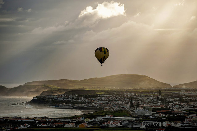 "A balloon flies during the I Azores hot air balloon festival ""Feel the Sky"", Ribeira Grande, Sao Miguel Island, Azores, Portugal, 01 July 2015. Twenty ballooning teams from several countries are taking part in the event. (Photo by Eduardo Costa/EPA)"
