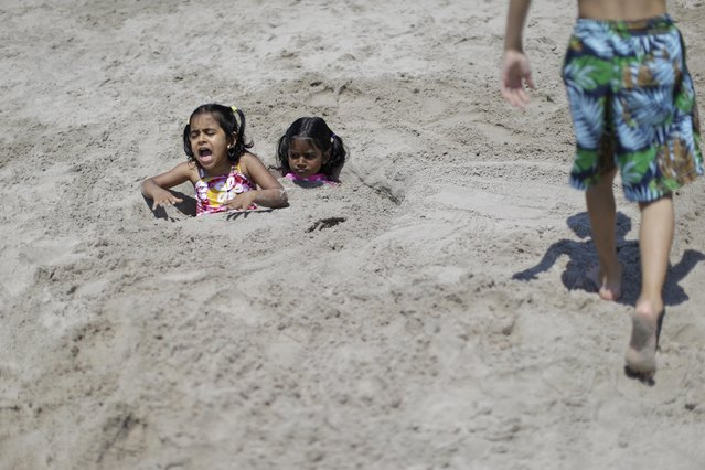 Sanskruti Nikam, 5, left, and Sarakshi Vhotkar, 4, both of Jersey City, N.J., are buried in the sand on Coney Island beach, Friday, July 3, 2015, in the Brooklyn borough of New York. Temperatures will be in the mid 70s and 80s for the 4th of July holiday weekend. (Photo by Mary Altaffer/AP Photo)