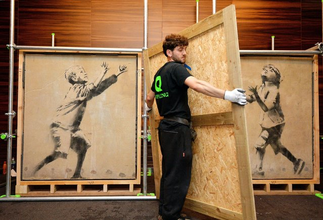 A section of wall graffiti artwork by  street artist Banksy, one of seven pieces of restored artwork is uncovered, as it goes on show to the public before an auction on Sunday April 27th, 2014 at the ME Hotel in central London. (Photo by John Stillwell/PA Wire)
