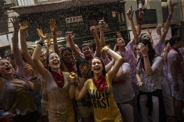 """Revelers are sprayed with water as they celebrate during the launch of the """"Chupinazo"""" rocket, to celebrate the official opening of the 2015 San Fermin fiestas in Pamplona, Spain, Monday, July 6, 2015. (Photo by Daniel Ochoa de Olza/AP Photo)"""