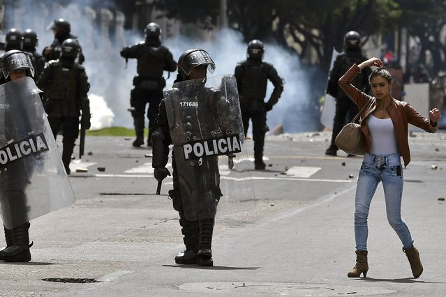 A woman straightens her hair as riot policemen stand in position during clashes within the first day of a national strike by farmers protesting against the government for alleged unpaid benefits, on April 28, 2014 in Bogota. (Photo by Luis Acosta/AFP Photo)