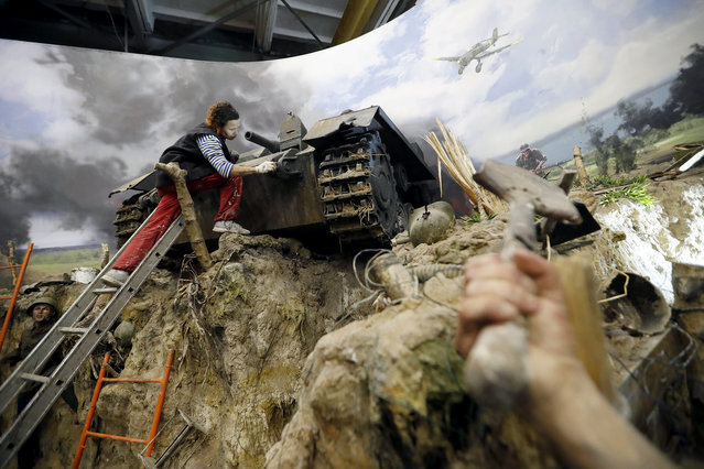 """A scene showing one of the first trench battles is prepared by a scenery worker (C) for the opening of the 3D Panorama exhibition """"Memory talks. The road through war"""" in the former Sevcabel port in St. Petersburg, Russia, 16 September 2019. (Photo by Anatoly Maltsev/EPA/EFE)"""