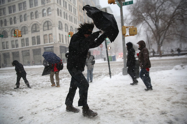 A man braces his umbrella while walking through the snow on February 13, 2014 in New York City. Heavy snow and high winds made for a hard morning commute in the city. (Photo by John Moore/Getty Images)