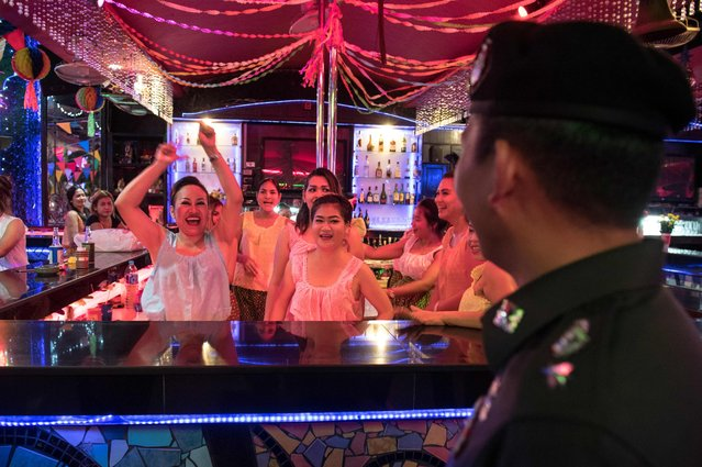 This photo taken on March 29, 2017 shows Thai Police Lieutenant Colonel Sulasak Kalokwilas (R) interacting with bartenders at an outside bar as he patrols Walking Street in Pattaya. (Photo by Roberto Schmidt/AFP Photo)