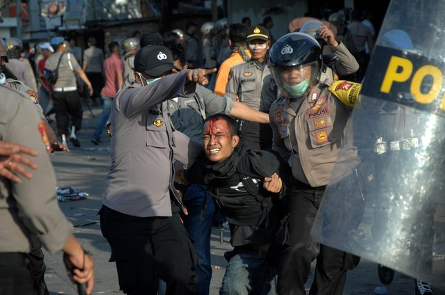 Police officers detain a protester during university students' protest outside the local parliament building in Makassar, South Sulawesi province, Indonesia on September 24, 2019. (Photo by Abriawan Abhe/Antara Foto via Reuters)