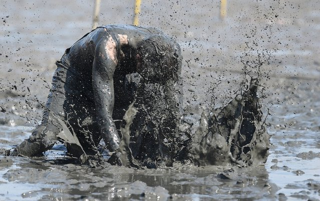"""A player reacts during a handball match at the so called """"Wattoluempiade"""" (Mud Olympics) in Brunsbuettel at the North Sea, July 11, 2015. (Photo by Fabian Bimmer/Reuters)"""