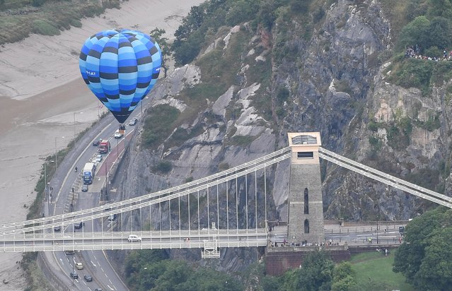 A balloon flies near the Clifton Suspension Bridge during a mass take off at the annual Bristol hot air balloon festival in Bristol, Britain, August 8, 2019. (Photo by Toby Melville/Reuters)