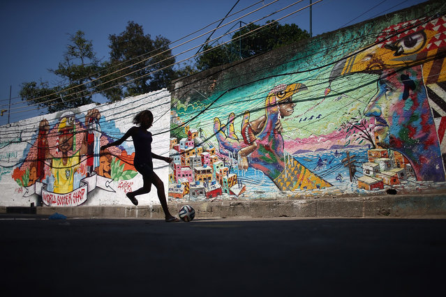 A girl plays soccer in front of graffiti created by acclaimed local graffiti artist Acme in the pacified Pavao-Pavaozinho community, on May 8, 2014 in Rio de Janeiro, Brazil. Protests and shootings broke out following the discovery of dancer Douglas Rafael da Silva Pereira's body in the 'favela' last month. (Photo by Mario Tama/Getty Images)