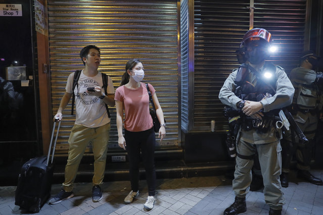 Pedestrians looks at Riot Police with face mask in the Tsim Sha Tsui district in Hong Kong, Thursday, October 10, 2019. A Hong Kong government official said on Thursday that Apple was responsible for removing a smartphone application which allowed activists to report police movements. (Photo by Kin Cheung/AP Photo)