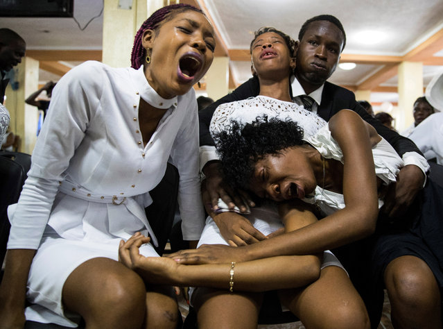 "Relatives of community leader Josemano ""Badou"" Victorieux, one of the victims of clashes with the Police, cry during his funeral in Port-au-Prince, Haiti, 16 October 2019. The protest movement in Haiti completes a month with no sign of remitting and without the President, Jovenel Moise, yielding to the voices that require him to resign. (Photo by Orlando Barria/EPA/EFE)"