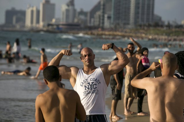 A Palestinian from Bethlehem flexes his muscles on a beach of the Mediterranean in Tel Aviv during Eid al-Fitr, which marks the end of the holy month of Ramadan July 19, 2015. (Photo by Baz Ratner/Reuters)