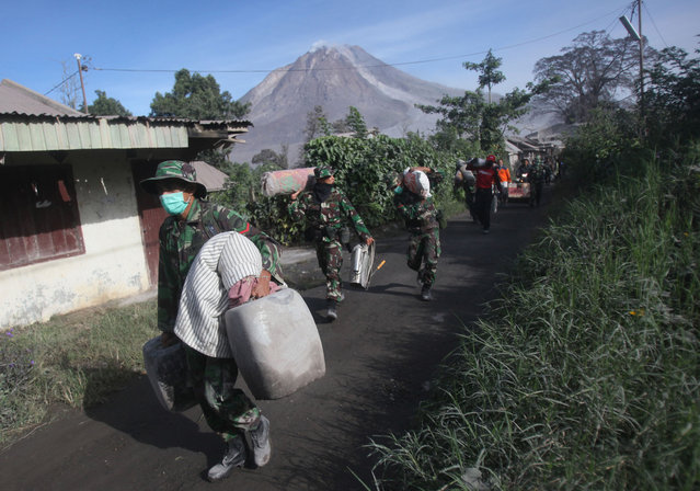 Indonesian soldiers carry people's belongings during an evacuation following the eruption of Mount Sinabung in Gamber village, North Sumatra, Indonesia, Sunday, May 22, 2016. (Photo by Binsar Bakkara/AP Photo)