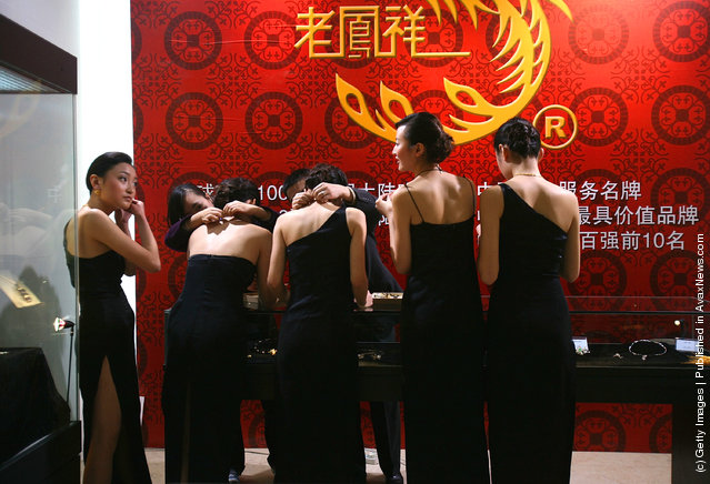Models wait to promote jewelry during a leading watch and jewelry show at Three Gorges Museum