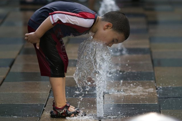 A child plays in water fountains at a shopping mall in Beijing, Monday, July 13, 2015. Chinese authorities issued a yellow alert for high temperatures as a heat wave sweeps parts of northern and central China. (Photo by Ng Han Guan/AP Photo)