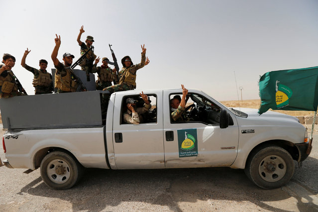 Shi'ite fighters ride on a vehicle near Falluja, Iraq, May 24, 2016. (Photo by Thaier Al-Sudani/Reuters)